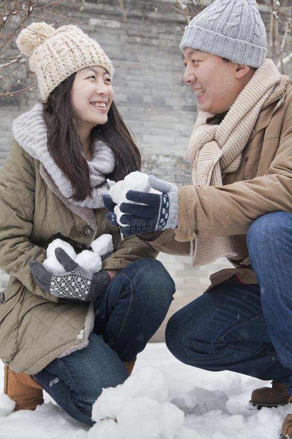Paare, die Schneebälle im Park halten lizenzfreies stockbild