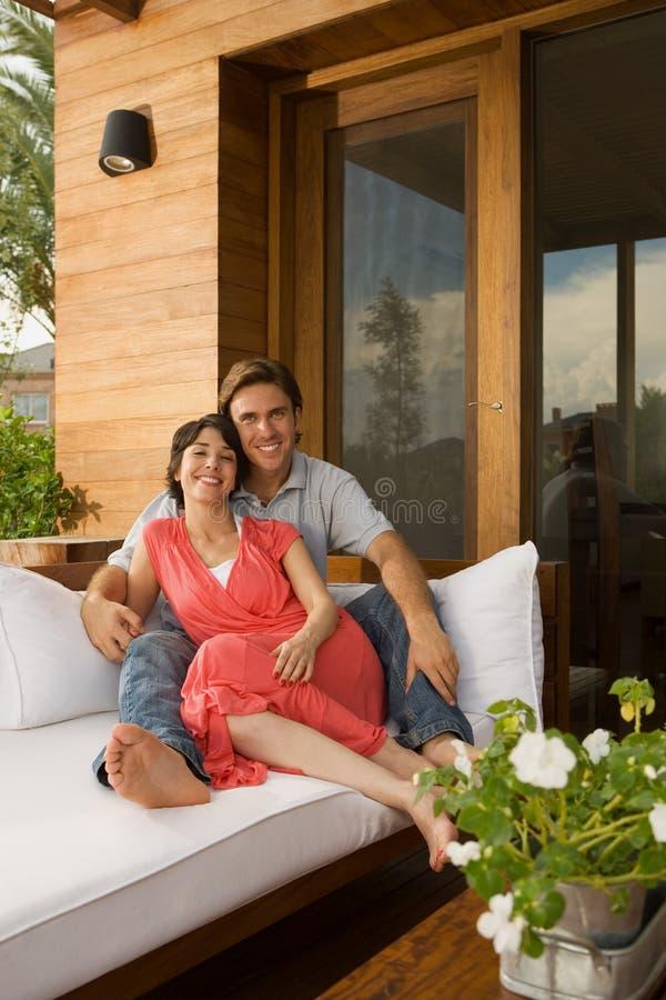 Paare, die sich draußen auf Sofa entspannen stockbilder
