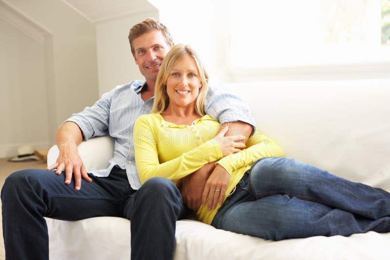 Paare, die sich zu Hause auf Sofa entspannen lizenzfreies stockbild