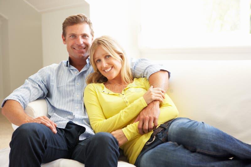 Paare, die sich zu Hause auf Sofa entspannen lizenzfreie stockfotografie