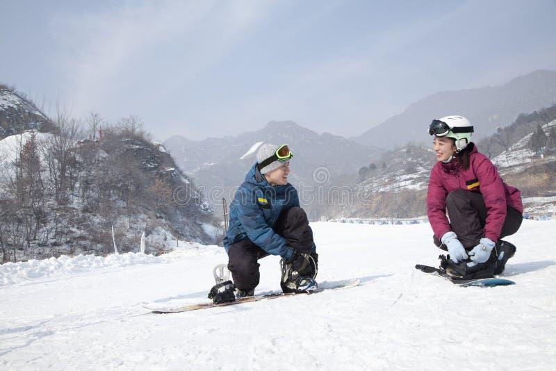 Paare, die Ski Boots in Ski Resort justieren stockfoto