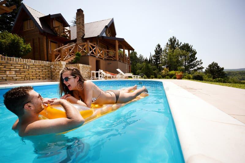 Paare, die Sommer im Pool genießen stockbild