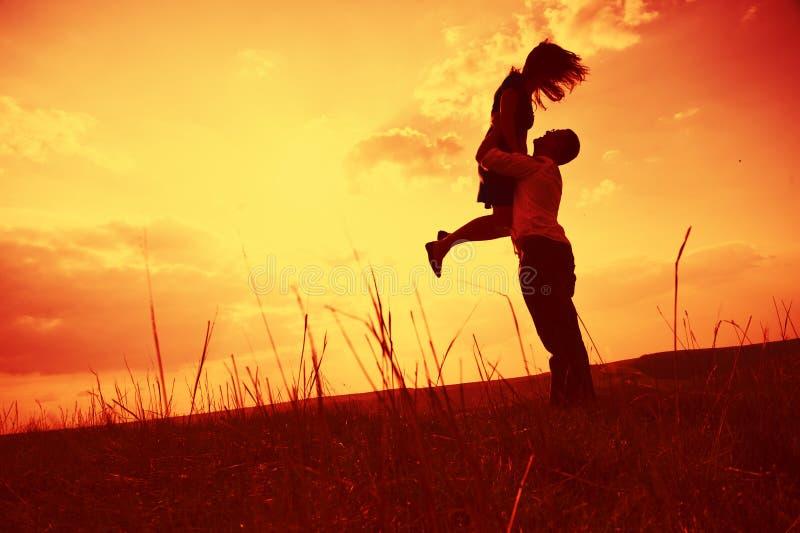 Paare, die am Sonnenuntergang umfassen lizenzfreie stockfotos