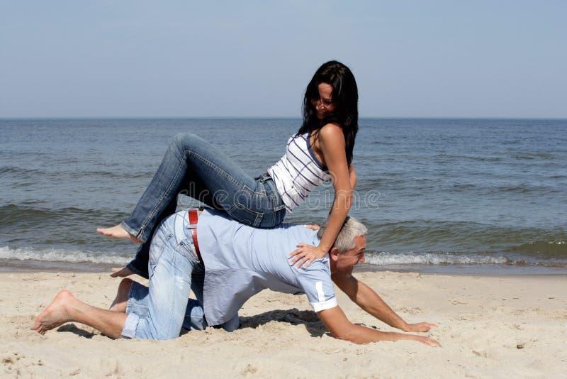 Paare, die Spaß auf dem Strand haben stockbilder