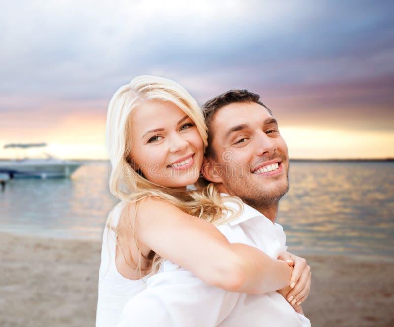 Paare, die Spaß haben und auf Strand umarmen lizenzfreies stockbild