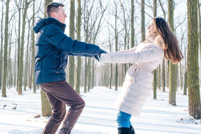 Paare, die Spaß im schneebedeckten Park haben stockbilder