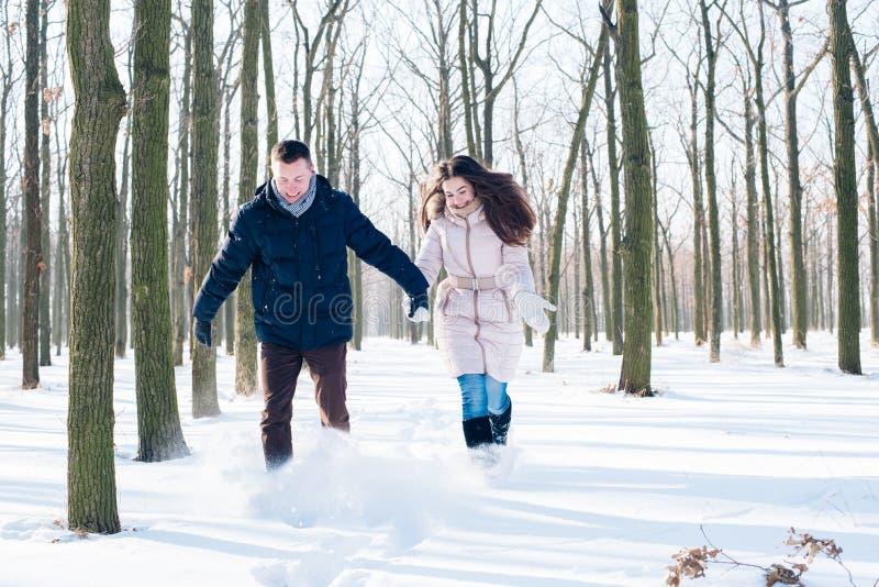 Paare, die Spaß im schneebedeckten Park haben stockfoto