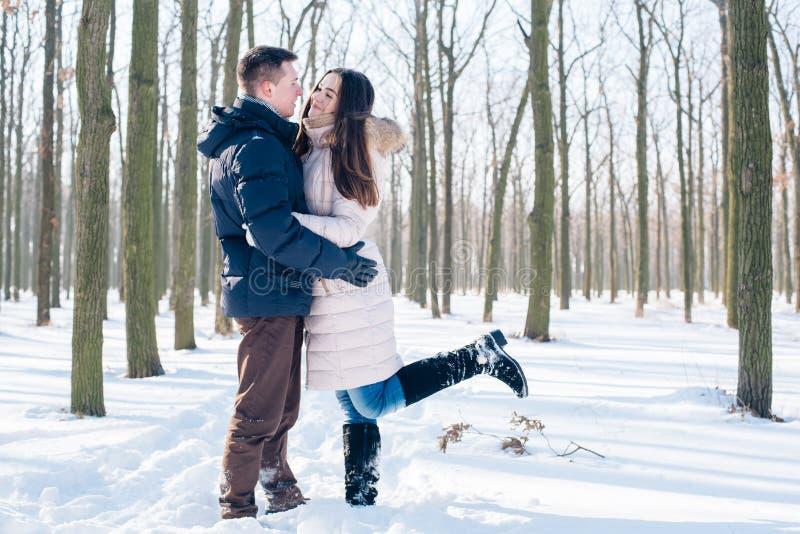 Paare, die Spaß im schneebedeckten Park haben stockfotografie