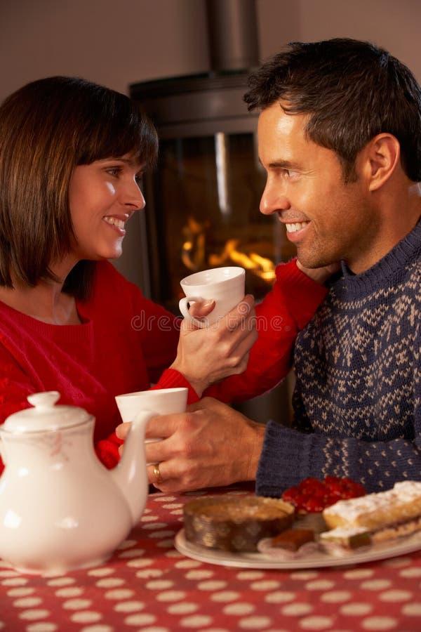 Paare, die Tee und Kuchen durch Cosy Protokoll-Feuer genießen stockfotografie
