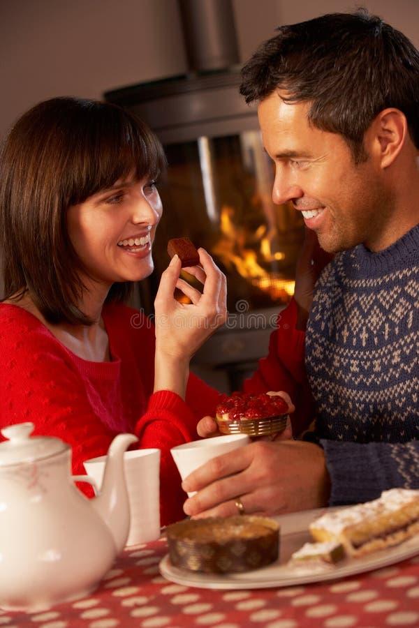 Paare, die Tee und Kuchen durch Cosy Protokoll-Feuer genießen lizenzfreies stockbild