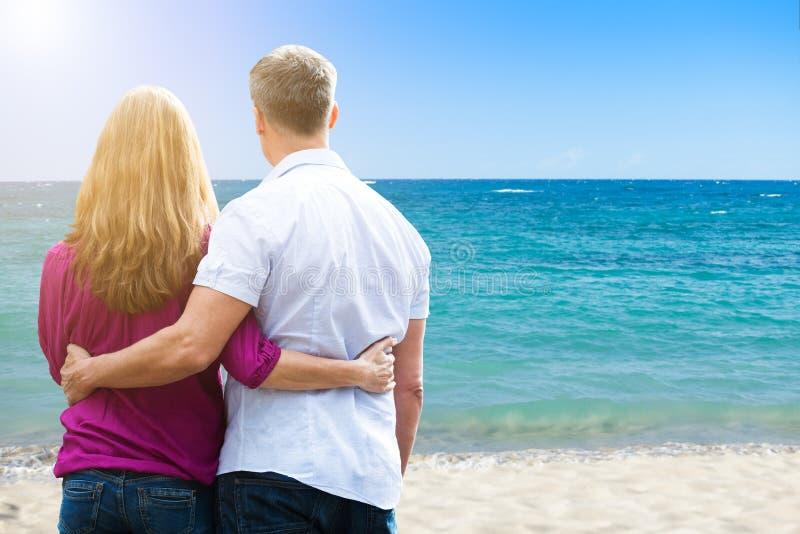 Paare, die am tropischen Strand stehen stockfotos
