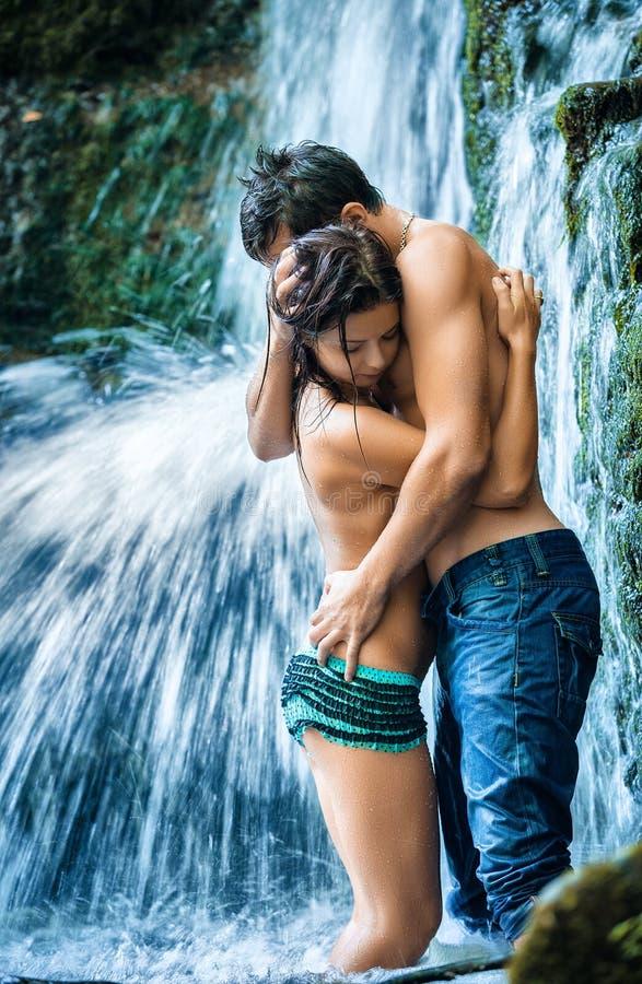 Paare, die unter Wasserfall umarmen und küssen stockbild