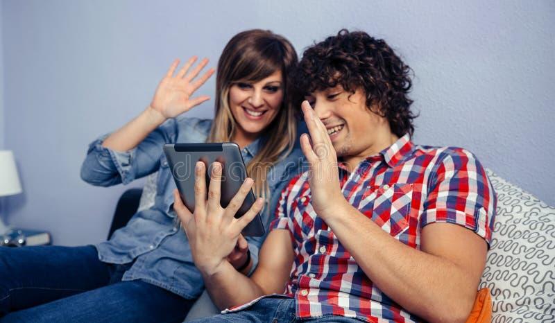 Paare, die Videoanruf mit der Tablette machen stockbilder