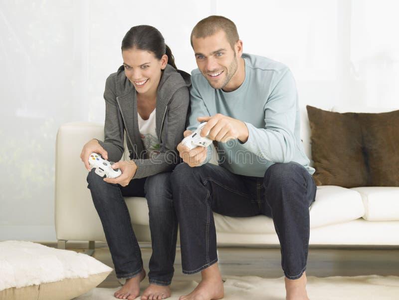 Paare, die Videospiel auf Sofa spielen lizenzfreies stockbild