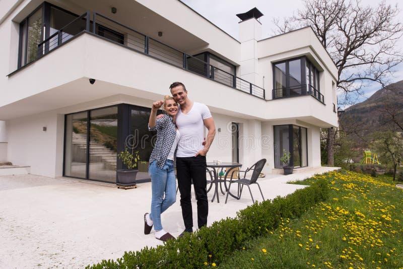 Paare, die vor neuem Luxushaus umarmen lizenzfreies stockfoto
