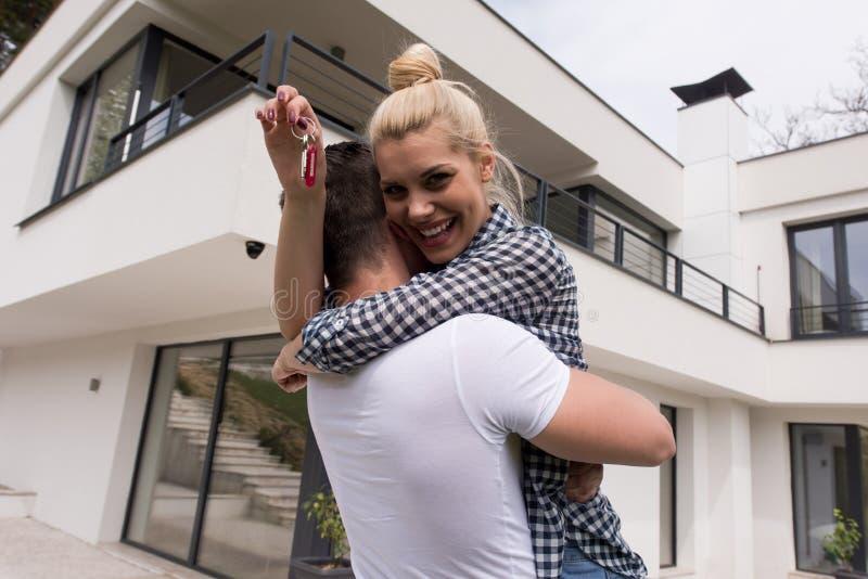 Paare, die vor neuem Luxushaus umarmen stockbild