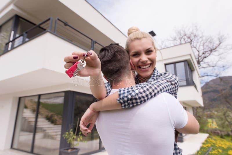 Paare, die vor neuem Luxushaus umarmen stockfotografie