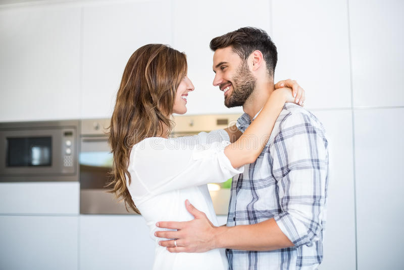 Paare, die vorbei in der Küche umfassen stockfotografie