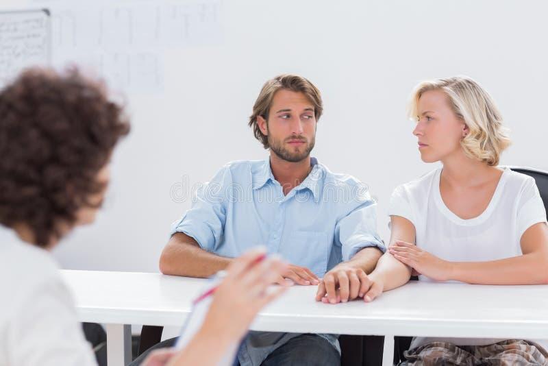 Paare, die während der Therapie-Sitzung zweifelhaft schauen lizenzfreie stockfotos