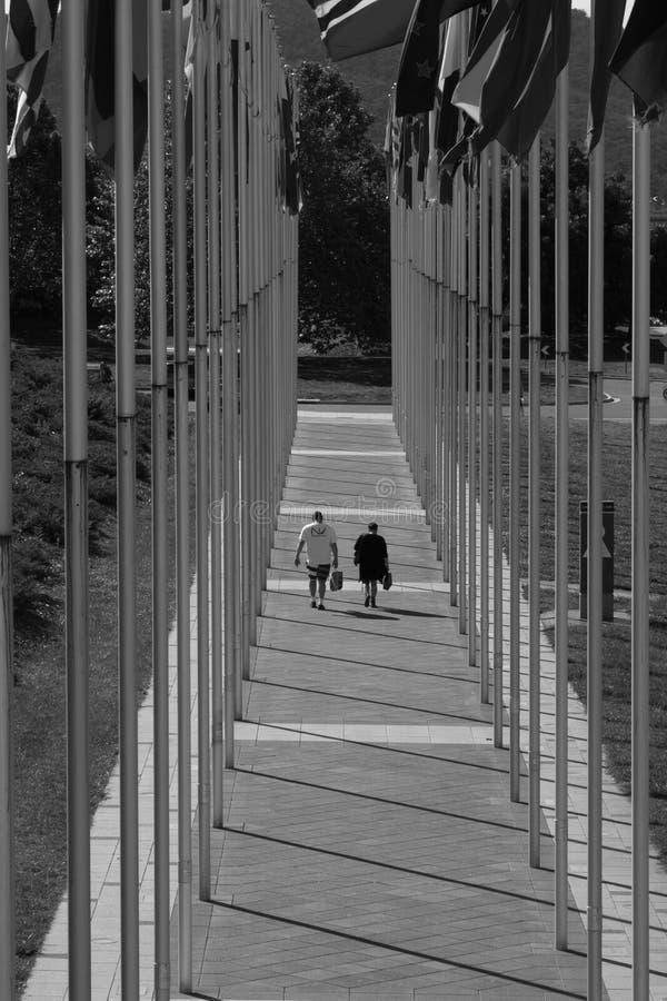 Paare, die weg zwischen Reihen von Fahnenmasten gehen stockfoto