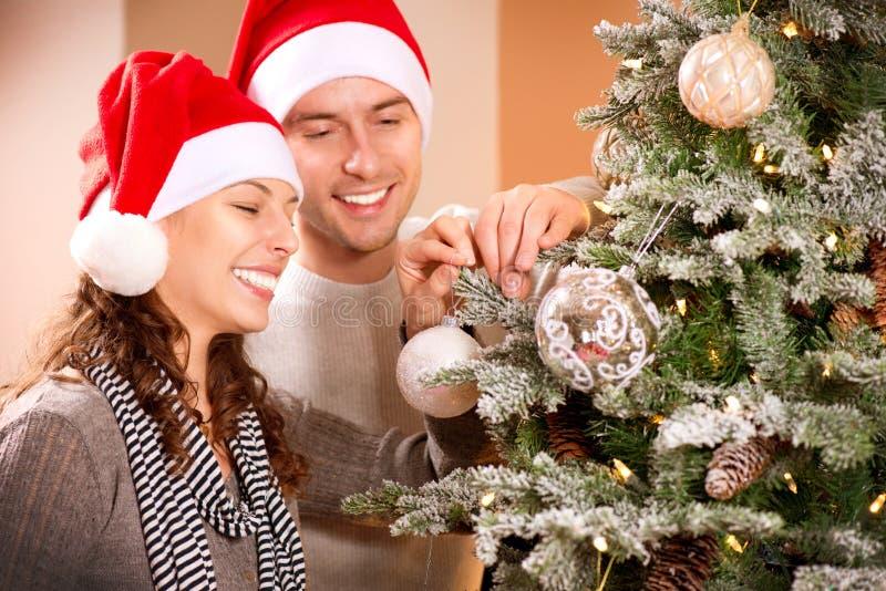 Paare, die Weihnachtsbaum verzieren stockbild