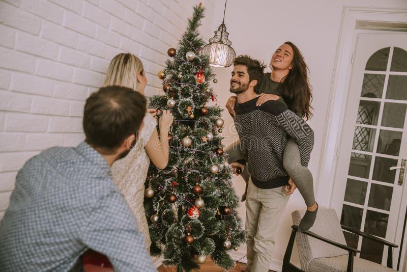 Paare, die Weihnachtsdekorationen auf dem Baum im Raum h?ngen stockbild
