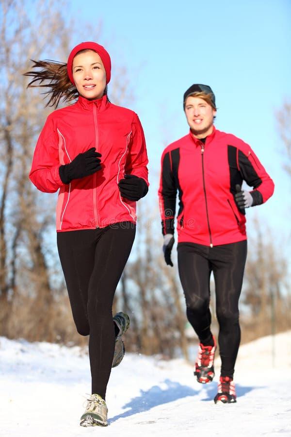 Paare, die in Winterschnee laufen