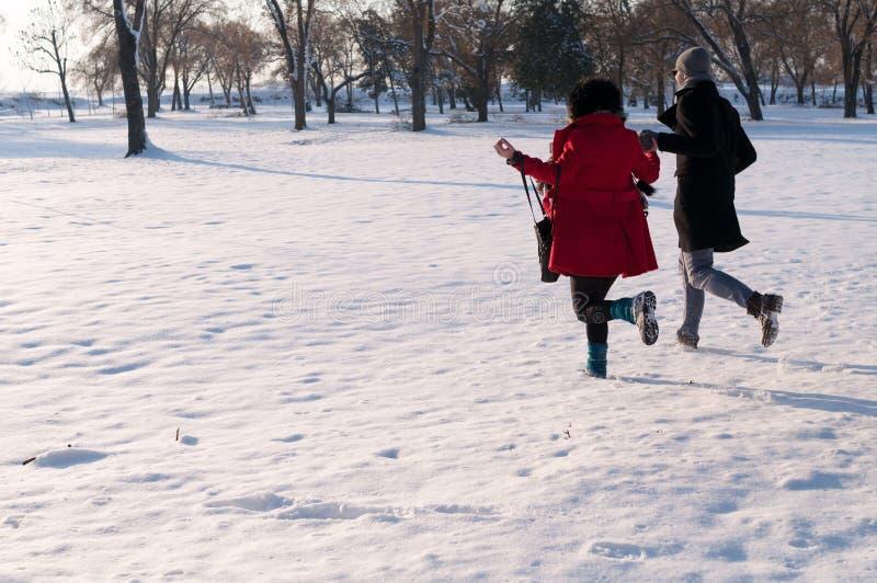 Paare, die in Winterwald laufen stockfoto