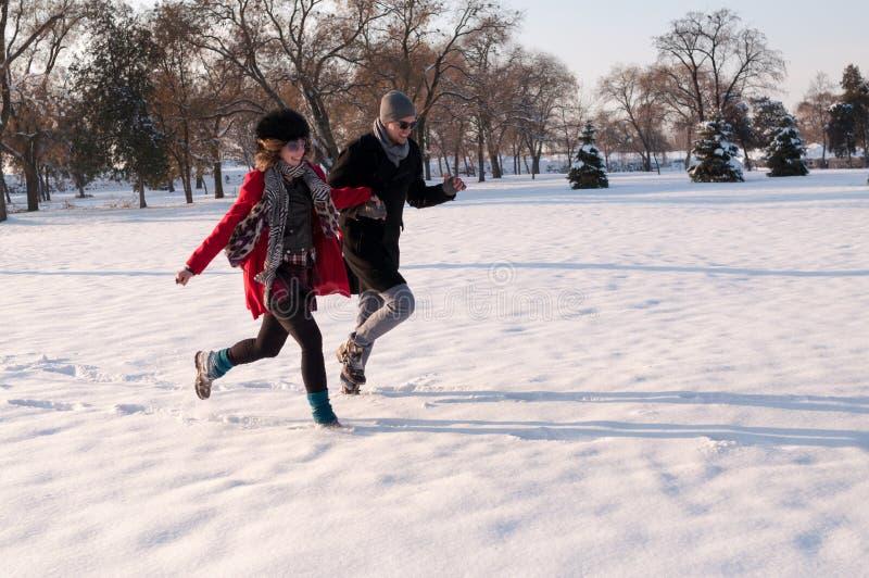 Paare, die in Winterwald laufen lizenzfreie stockfotos