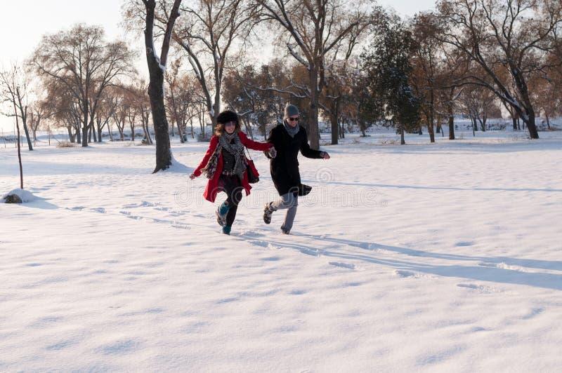 Paare, die in Winterwald laufen lizenzfreie stockfotografie