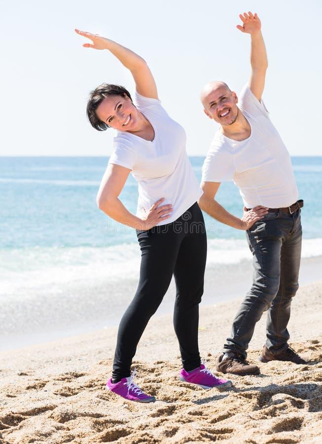 Paare, die Yoga auf dem Strand tun stockfoto