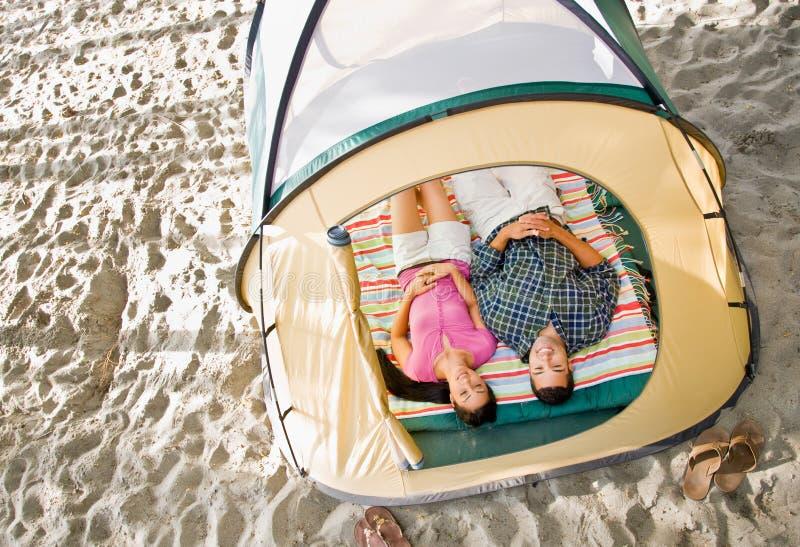 Paare, die in Zelt legen lizenzfreie stockbilder