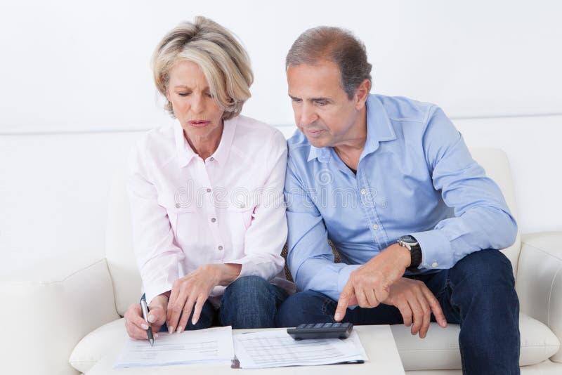 Paare, die zu Hause Familienfinanzen tun lizenzfreie stockbilder