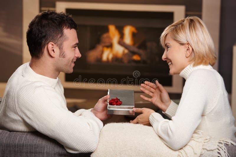 Paare, die zu Hause Geschenk austauschen stockfotos