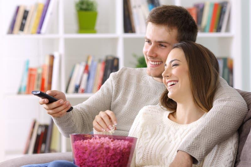 Paare, die zu Hause im Winter fernsehen lizenzfreies stockbild