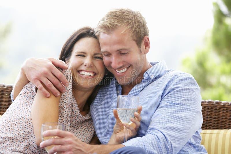 Paare, die zusammen auf Seat im Freien sitzen lizenzfreies stockbild