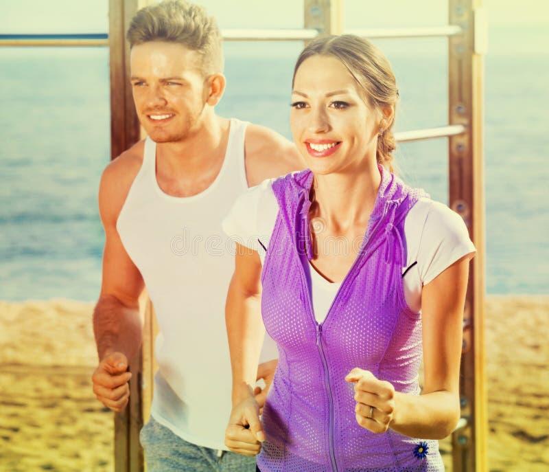 Download Paare, Die Zusammen Auf Strand Durch Ozean Laufen Stockfoto - Bild von paßsitz, mann: 90235320