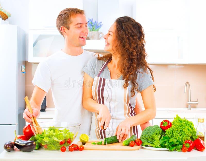 Paare, die zusammen in ihrer Küche kochen stockbild