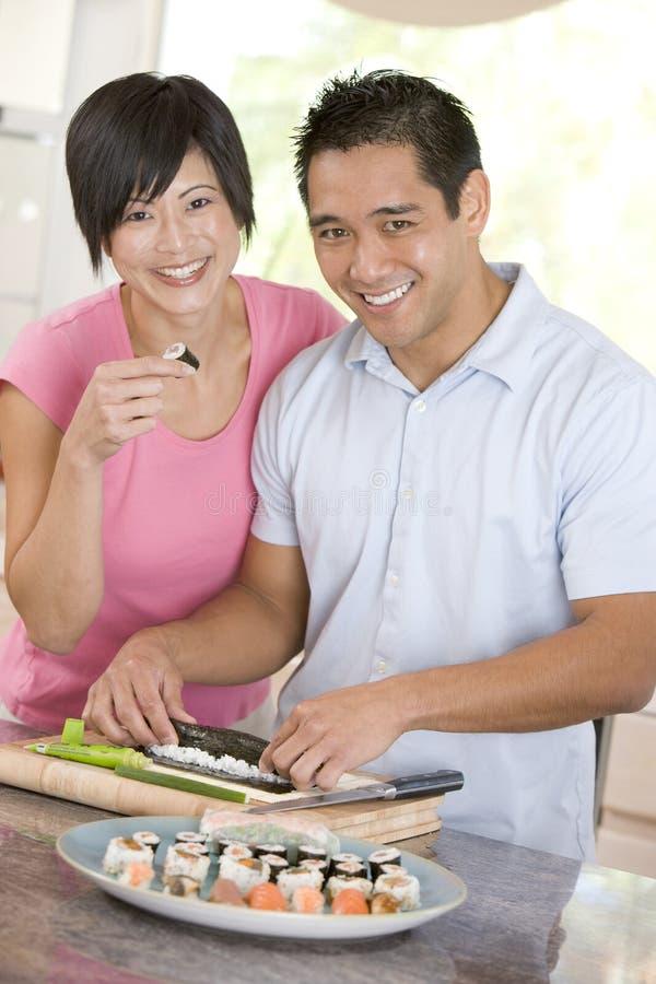Paare, die zusammen Sushi zubereiten stockfotografie