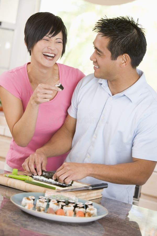 Paare, die zusammen Sushi zubereiten lizenzfreies stockfoto