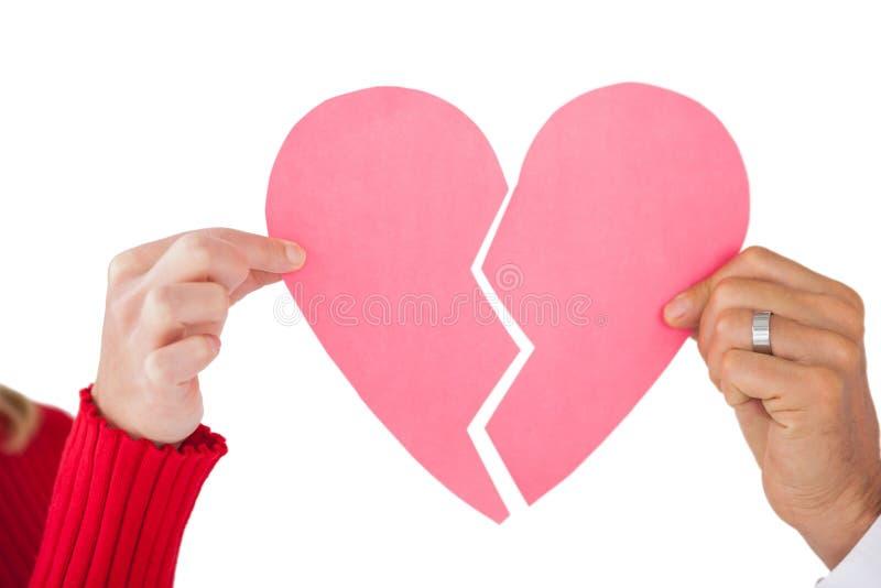 Paare, die zwei Hälften des defekten Herzens halten stockfoto
