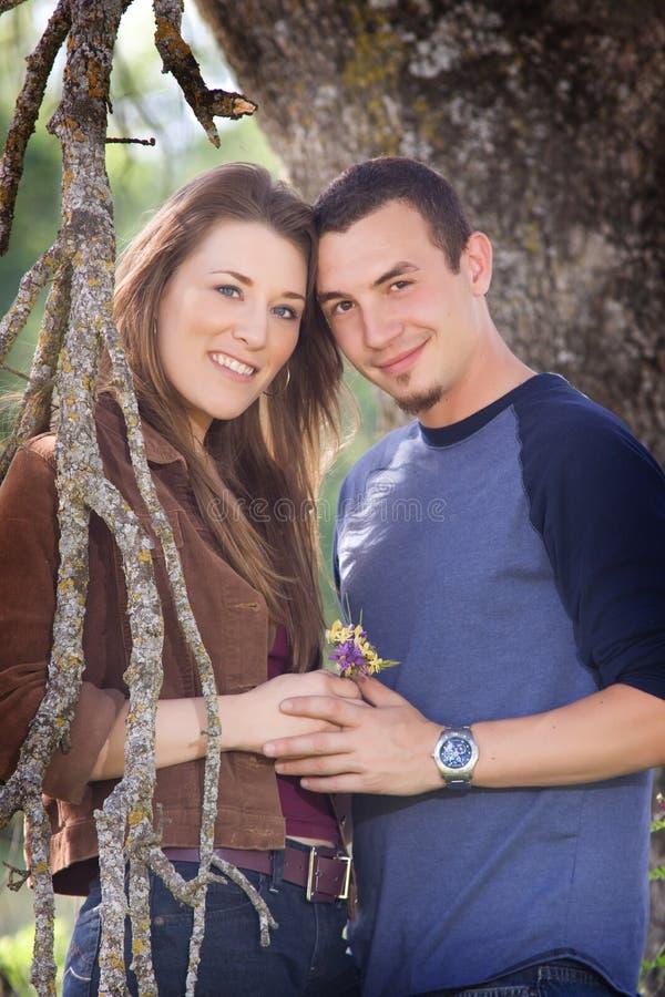 Paare durch Baum mit Blumen lizenzfreie stockfotografie