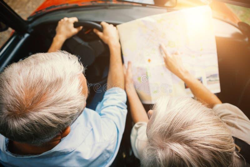 Paare in einem Auto, das eine Straßenkarte betrachtet lizenzfreie stockbilder