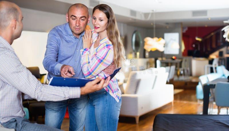 Paare entsetzt vom Schauen durch Preisliste stockfoto