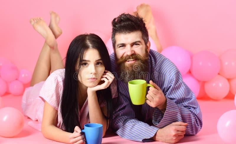 Paare entspannen sich am Morgen mit Kaffee Mann und Frau auf lächelnder Gesichtslage, rosa Hintergrund Wochenendenmorgenkonzept lizenzfreies stockbild