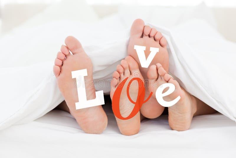 Paare Füße unter Daunendecke mit Liebe simsen stockfotos