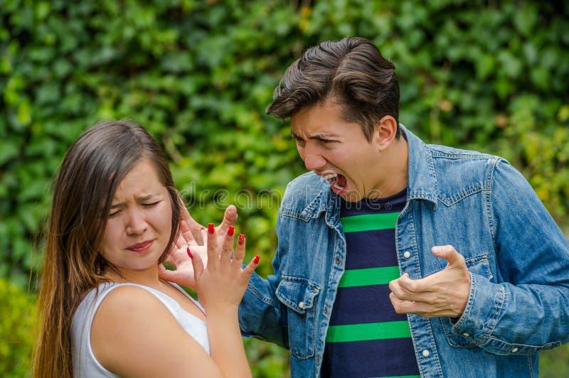 Paare Fighting Ein junger Mann, der eine junge Frau während die Blicke der jungen Frau erschrocken, friendzone Konzept schreit lizenzfreie stockfotografie