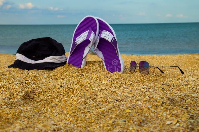 Paare Flipflops, Hut und Sonnenbrille auf einem sandigen Meer setzen auf den Strand stockfotografie