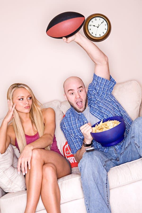 Paare: Frau ermüdet von Mann-aufpassendem Sport lizenzfreies stockbild