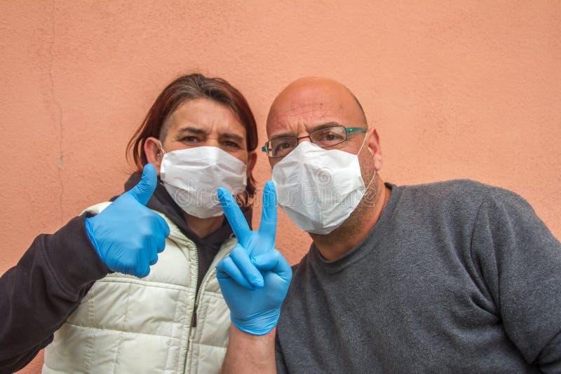 Paare Frauen und Männer mit ärztlicher Maske und Handschuhen des blauen Arztes weisen auf das richtige Anzeichen für das Virus hi lizenzfreies stockbild